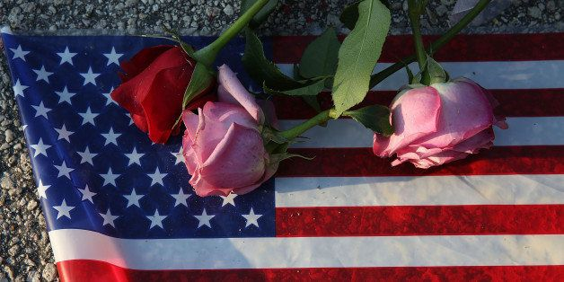 ORLANDO, FL - JUNE 13:  Flowers and an American flag are seen on the ground near the Pulse Nightclub where Omar Mateen allege