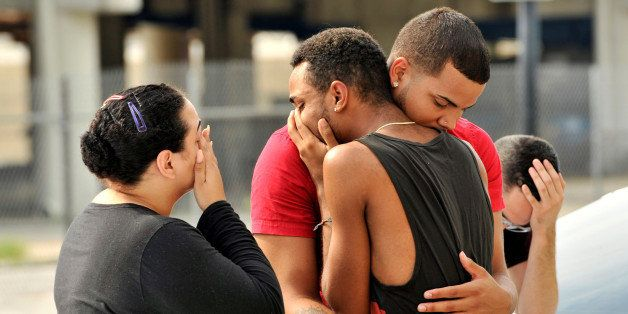 Friends and family members embrace outside the Orlando Police Headquarters during the investigation of a shooting at the Puls