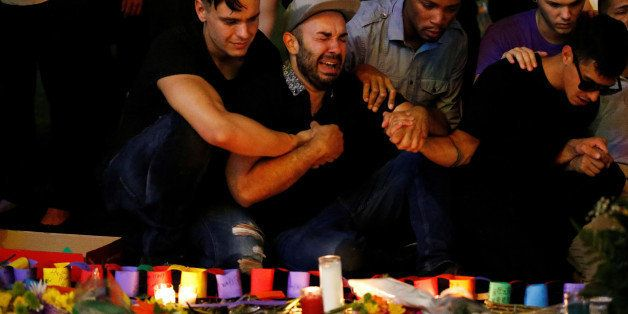 A man sits and cries after taking part in a candlelight memorial service the day after a mass shooting at the Pulse gay night