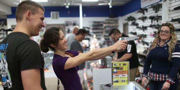 POMPANO BEACH, FL - DECEMBER 23:  Vesta Parks checks out a handgun as she prepares to buy Tim Schneider (L) one as a Christma