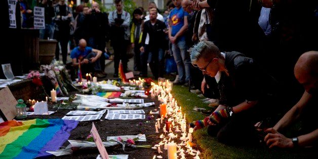 People pay their respects and place candles and tributes at Saint Anne's Church in the Soho district of central London, durin