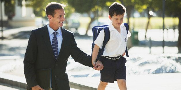 Businessman and son holding hands in urban park