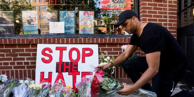STONEWALL INN, MANHATTAN, NEW YORK, NY, UNITED STATES - 2016/06/12: An attendee of the rally places a bouquet of flowers at a