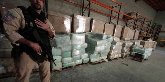 An agent from the U.S. Immigration and Customs Enforcement (ICE) stands guard in front of blocks of marijuana in an industria