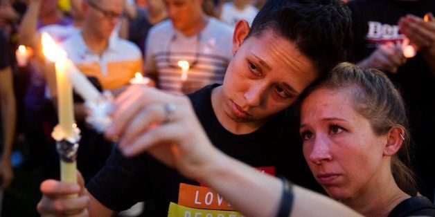FILE - In this Monday, June 13, 2016 file photo, Jennifer, right, and Mary Ware light candles during a vigil in Orlando, Fla.