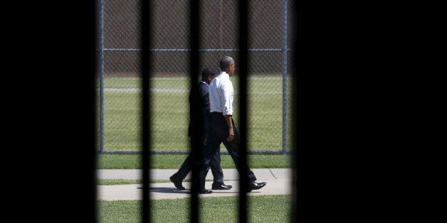 Photographed through a prison cell window, U.S. President Barack Obama tours the El Reno Federal Correctional Institution aft