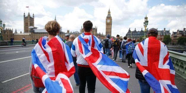 People walk over Westminster Bridge wrapped in Union flags, towards the Queen Elizabeth Tower (Big Ben) and The Houses of Par
