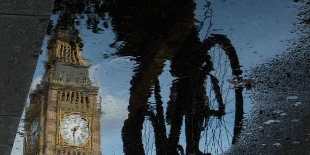The Queen Elizabeth Tower (Big Ben) is reflected in a puddle as a cyclist rides by in London, on 27 June 2016. Britain began