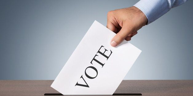Close up of male hand putting vote into a balot box