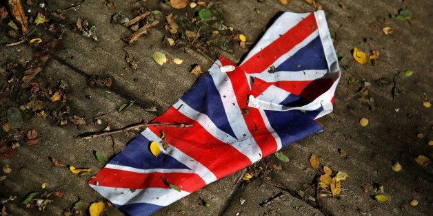 A British flag which was washed away by heavy rains the day before lies on the street in London, Britain, June 24, 2016 after
