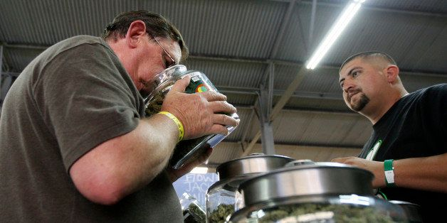 A medical marijuana user smells a jar of marijuana at the medical marijuana farmers market at the California Heritage Market