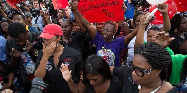 Community members attend a vigil in memory of Alton Sterling, who was shot dead by police, at the Triple S Food Mart in Baton