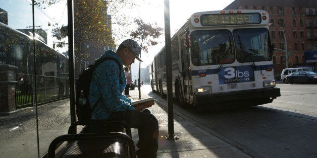 Teenage boy (15-17) at bus stop reading book