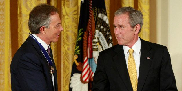 Former British Prime Minister Tony Blair (L) receives the Presidential Medal of Freedom from U.S. President George W. Bush du