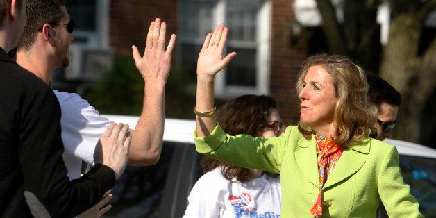 Katie McGinty greets supporters with high-fives as she arrives at her polling station to cast her vote Tuesday, April 26, 201