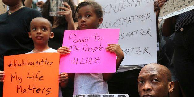 Jashaun Sadler, right, and his twins Malik, left, and Jazlin Sadler listen to speakers during a Black Lives Matter demonstrat