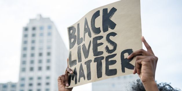 A protestor holds up a sign reading 'Black Lives Matter' during a demonstration in Berlin, on July 10, 2016 with the motto 'B