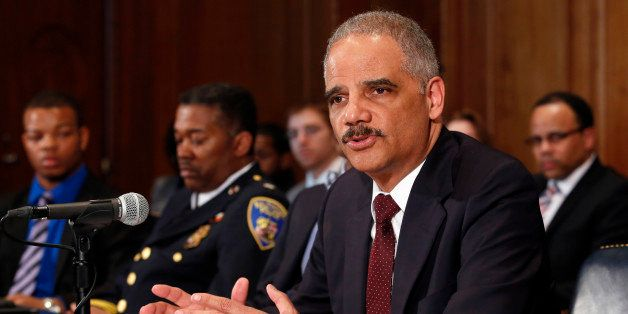 U.S. Attorney General Eric Holder arrives to talk to the media about the shooting of two police officers in Ferguson, and to