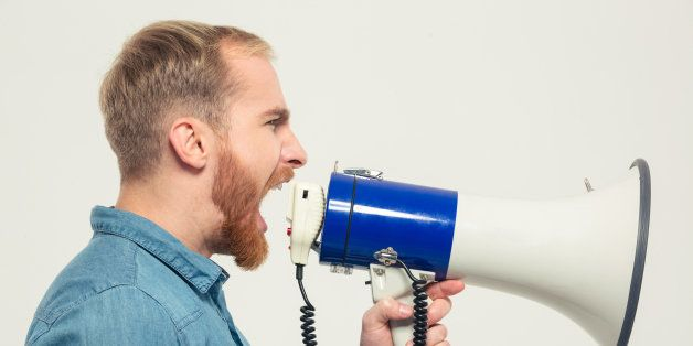 Side view portrait of a casual man yelling into megaphone isolated on a white background