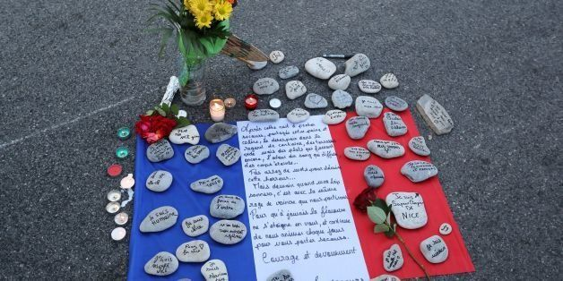 This photo taken on July 16, 2016 in Nice shows a make-shift memorial made of France's flag and messages written on stones le