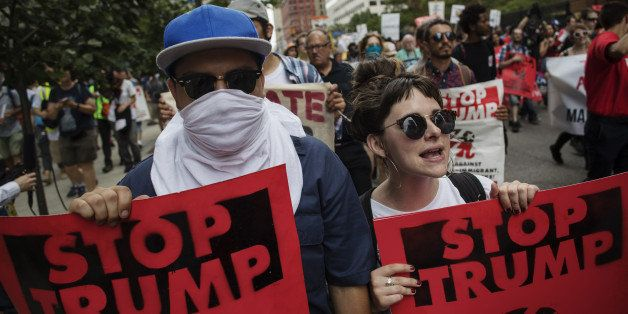 Protesters march while holding 'Stop Trump' signs during a demonstration at the Republican National Convention (RNC) in Cleve