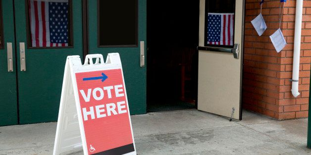 Stock photo of a vote here sign at an American voting location with American flags in the background
