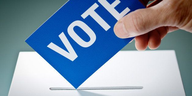 Voter's hand holding election ballot for the U.S. Democratic Party, inserting the vote into the ballot box. Concept image of