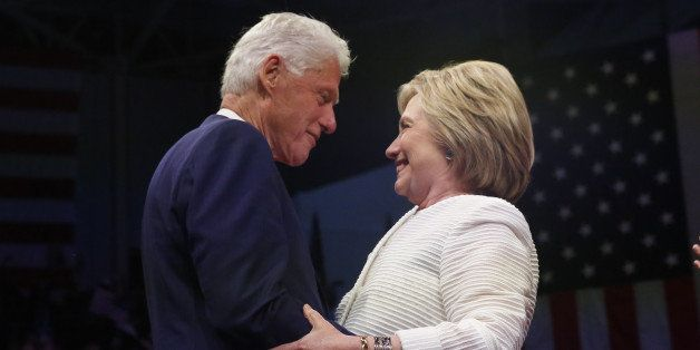 Democratic U.S. presidential candidate Hillary Clinton stands onstage with her husband former President Bill Clinton (L) afte