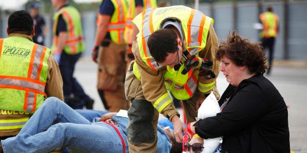 First responders work with volunteers pretending to be victims in a simulated airplane crash during a full-scale emergency pr