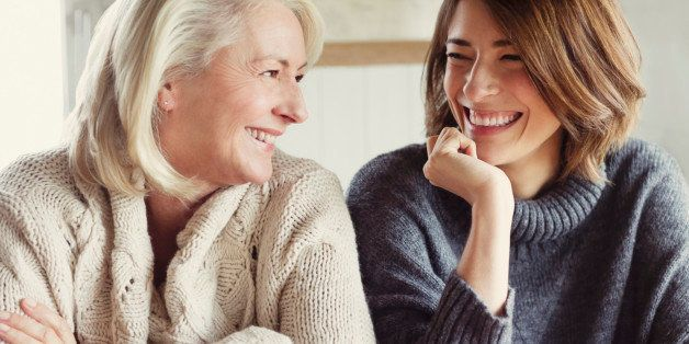 Laughing mother and daughter in sweaters drinking coffee