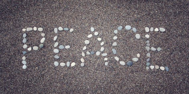 'Peace' word written with pebbles on the sand. Aged photo. 'Peace' word made by small stones on the beach. Word on the sand -