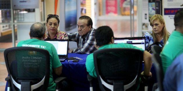 MIAMI, FL - DECEMBER 11:  Marlene Gonzalez (L) sits with Alberto Gonzalez (C) as they and Marinely Perez (R) speak with insur