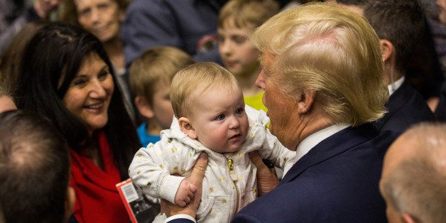 PORTSMOUTH, NH - FEBRUARY 04:  Republican presidential hopeful Donald Trump holds a baby the end of a rally at Great Bay Comm