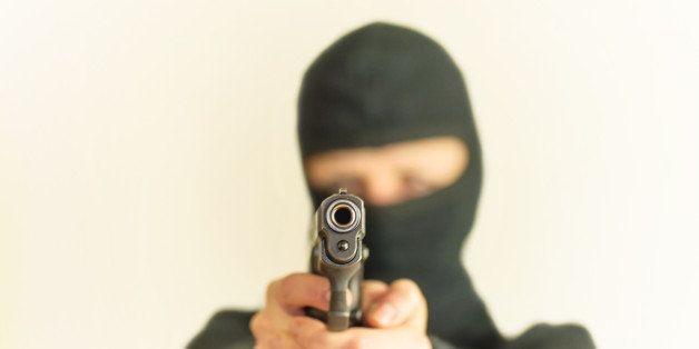 masked man points a gun