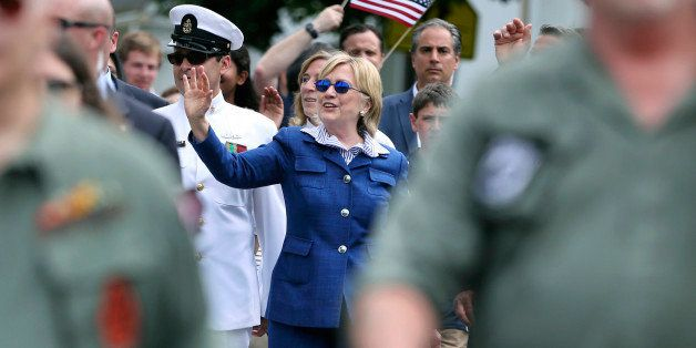 Democratic presidential candidate Hillary Clinton waves as she walks behind marching veterans in a Memorial Day parade Monday