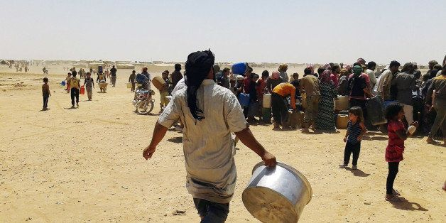 In this Tuesday, June 28, 2016 photo, Syrian refugees gather for water at Ruqban border camp in northeast Jordan. Syrian refu