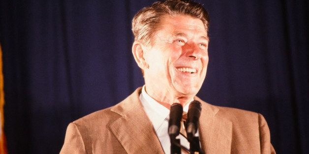 During his presidential campaign, American politician (and future US President) Ronald Reagan (1911 - 2004) smiles from behin