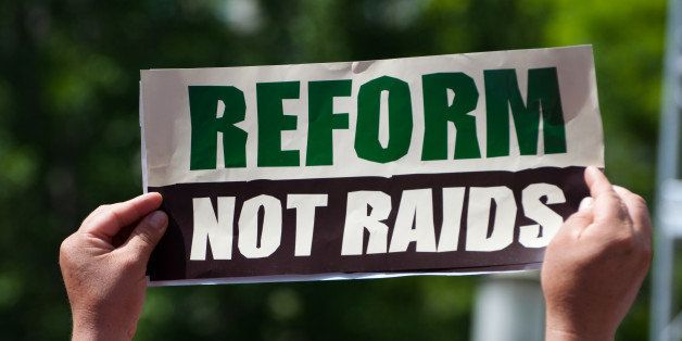 Immigration reform activists protest with a sign reading 'Reform Not Raids.'