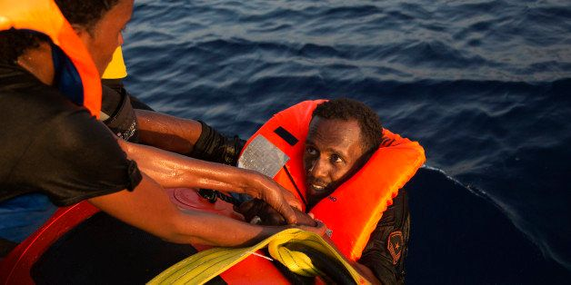 A migrant from Eritrea is helped after jumping into the water from a crowded wooden boat during a rescue operation in the Med