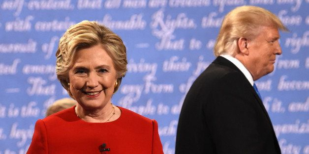 TOPSHOT - Democratic nominee Hillary Clinton (L) and Republican nominee Donald Trump leave the stage after the first presiden