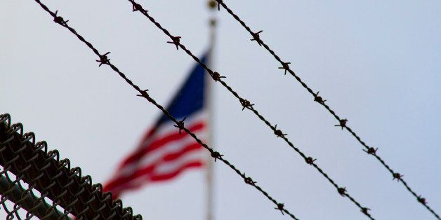 An American flag behind a barbwire fence. May symbolize prison, political messages, or loss of freedom.