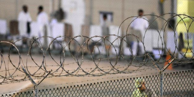 A Navy guard patrols Camp Delta?s detainee recreation yard during the early morning at Guantanamo Bay naval base in a July 7,
