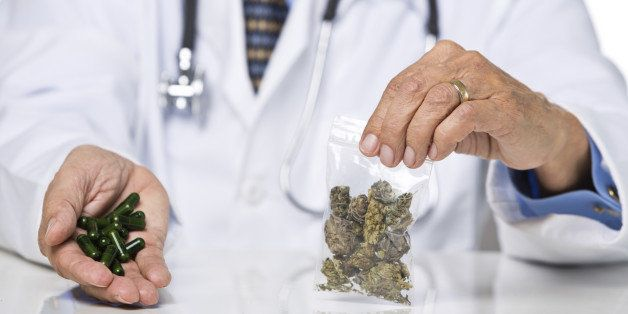 Unrecognizable male wearing lab coat and stethoscope holding pills and marijuana, isolated on white background, selective focus