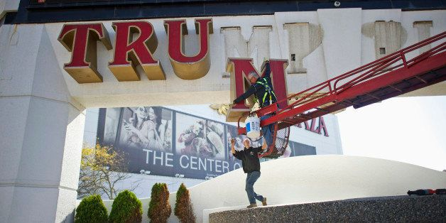 Jim Williams, of Calvi Electric, lowers the letter 'M' from the signage of Trump Plaza Casino to his co-worker Steven Nordaby