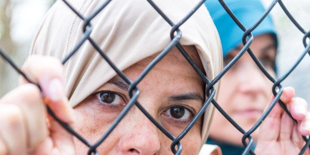 Middle eastern mature women posing looking looking through a fence very sad