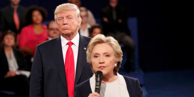 Republican U.S. presidential nominee Donald Trump listens as Democratic nominee Hillary Clinton answers a question from the a