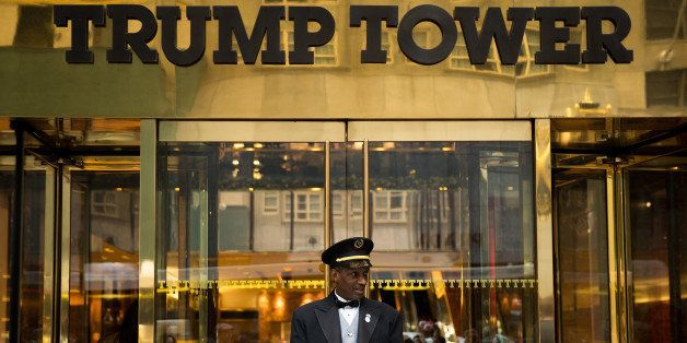 NEW YORK, NEW YORK - SEPTEMBER 29: A doorman stands at the entrance of Trump Tower as protestors rally against Republican pre