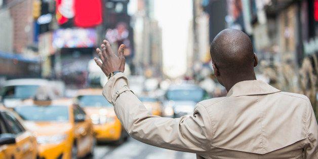 Black businessman hailing taxi on city street