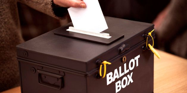 Person places their vote in a ballot box at a polling station.