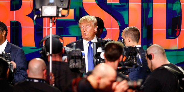 Republican U.S. presidential candidate Donald Trump is surrounded by TV technicians and cameras at the conclusion of the deba